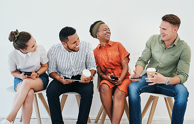 Buy stock photo Cropped shot of a diverse group of businesspeople sitting against a gray background together and using technology in the office