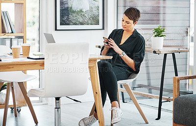 Buy stock photo Full length shot of an attractive young businesswoman sitting alone and texting on her cellphone in the office