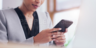 Buy stock photo Cropped shot of an unrecognizable businesswoman using a smartphone while working in her office during the day