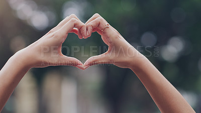 Buy stock photo Cropped shot of an unrecognizable businesswoman making a heart shape with her hands while standing outdoors in the city