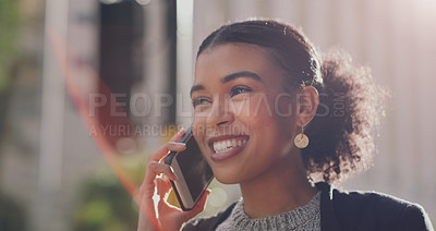 Buy stock photo Cropped shot of an attractive young businesswoman smiling while taking a phonecall outdoors in the city