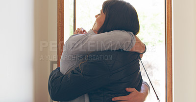 Buy stock photo Cropped shot of an affectionate young man welcoming his wife home while standing in front of their front door