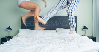 Buy stock photo Cropped shot of an unrecognizable couple playfully jumping on their bed in their bedroom at home
