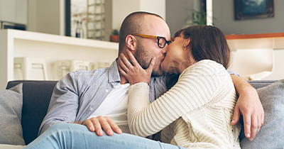 Buy stock photo Cropped shot of an affectionate young couple kissing each other while sitting on a couch in their living room at home