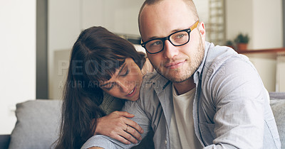 Buy stock photo Cropped shot of an affectionate young woman embracing her upset husband while sitting on a couch in their living room at home