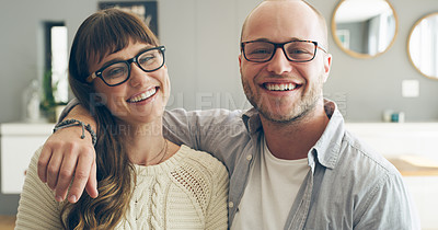 Buy stock photo Cropped portrait of an affectionate young couple smiling while spending time together indoors at home
