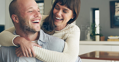 Buy stock photo Cropped shot of an affectionate young man piggybacking his wife in their kitchen at home