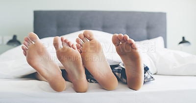 Buy stock photo Cropped shot of an unrecognizable couple's feet lying next to each other in their bed at home