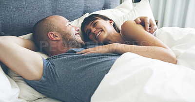 Buy stock photo Cropped shot of an affectionate young couple smiling at each other while lying in their bed at home