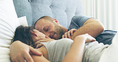 Buy stock photo Cropped shot of an affectionate young couple sharing an intimate moment while lying in bed at home