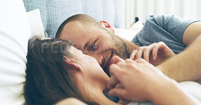 Buy stock photo Cropped shot of an affectionate young man smiling at his wife while lying in bed at home