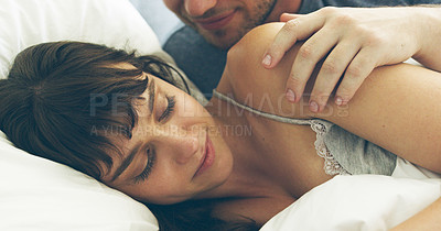 Buy stock photo Cropped shot of an unrecognizable man waking his wife up while lying in bed at home