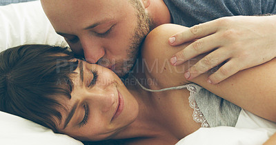 Buy stock photo Cropped shot of an affectionate young man kissing his wife while lying in bed at home