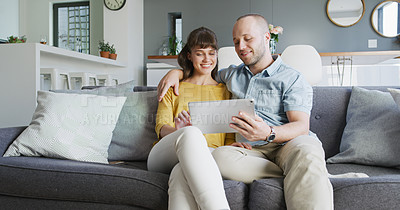 Buy stock photo Cropped shot of an affectionate young couple using a digital tablet together while relaxing in their living room at home