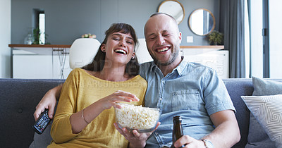 Buy stock photo Cropped shot of an affectionate young couple having beer and popcorn while enjoying a television show together at home