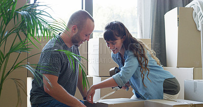 Buy stock photo Cropped shot of an affectionate young couple using adhesive tape while packing up boxes on moving day