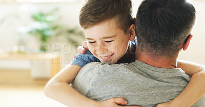 Buy stock photo Shot of a little boy hugging his father at home