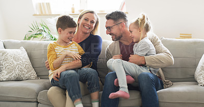 Buy stock photo Shot of a happy family sitting on the couch together at home