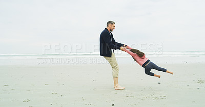 Buy stock photo Shot of a father swinging his little daughter at the beach