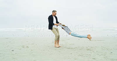 Buy stock photo Shot of a father swinging his little son at the beach
