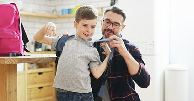 Buy stock photo Shot of a father helping his son put on a backpack before leaving for school