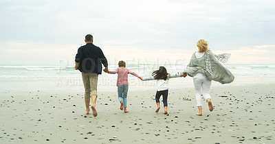 Buy stock photo Rearview shot of a family running along the beach