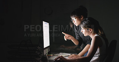 Buy stock photo Shot of two businesswomen working together on a computer in an office at night