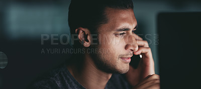 Buy stock photo Shot of a young businessman talking on a cellphone while working on a computer in an office at night