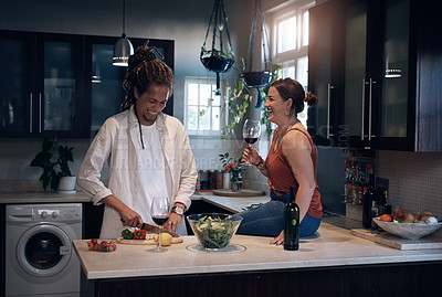 Buy stock photo Shot of a young couple bonding in the kitchen while preparing a salad