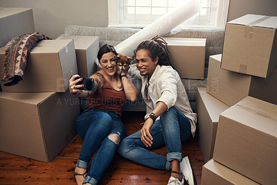 Buy stock photo Shot of a young couple taking a selfie while busy moving into their new home