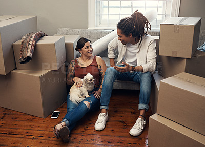 Buy stock photo Shot of a couple sitting with their dog while taking a break on moving day