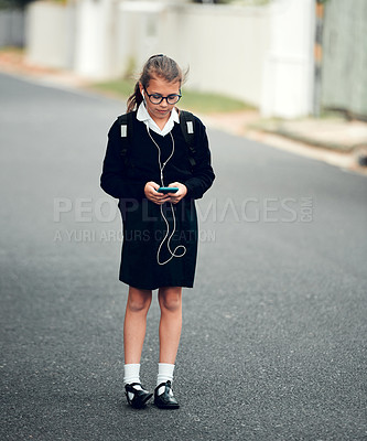Buy stock photo Full length shot of a young schoolgirl listening to music and using her cellphone while walking to school