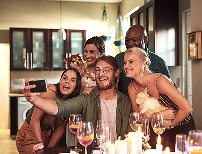 Buy stock photo Cropped shot of a group of cheerful young friends taking a self portrait together with a cellphone during a dinner party at home