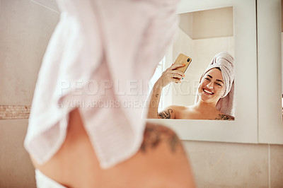 Buy stock photo Shot of a young woman taking a selfie while going through her morning beauty routine