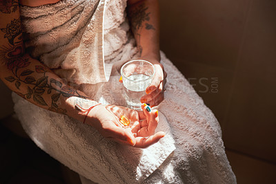 Buy stock photo Cropped shot of a woman taking a pill with a glass of water during her morning routine at home