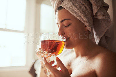 Buy stock photo Shot of a young woman having tea while going through her morning beauty routine at home