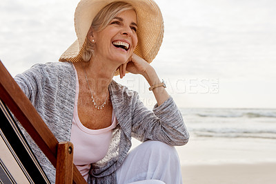 Buy stock photo Cropped shot of an attractive middle aged woman sitting on a lounger at the beach