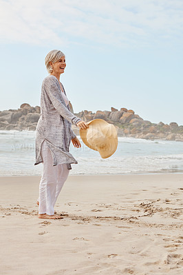 Buy stock photo Full length shot of an attractive middle age woman walking along the beach