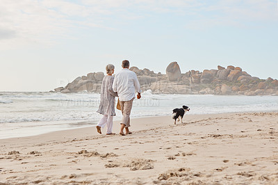 Buy stock photo Rearview shot of an affectionate middle aged couple walking hand in hand with along the beach with their dog