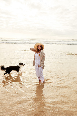 Buy stock photo Portrait of a young woman spending some time with her dog at the beach