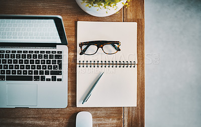 Buy stock photo Still life shot of a laptop and a notebook placed on a desk at an office workstation