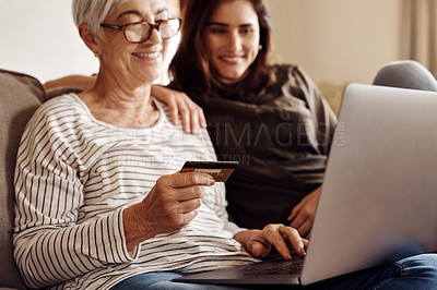 Buy stock photo Shot of a young woman using a laptop and credit card with her elderly mother on the sofa at home