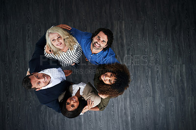Buy stock photo High angle shot of a group of businesspeople huddled together in solidarity in a modern office
