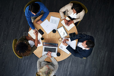 Buy stock photo High angle shot of colleagues shaking hands during a meeting in a modern office