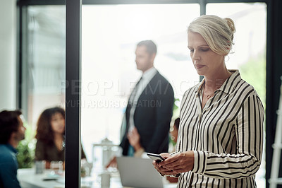 Buy stock photo Shot of a mature businesswoman using a cellphone in an office with her colleagues in the background