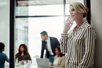 Buy stock photo Shot of a mature businesswoman talking on a cellphone in an office with her colleagues in the background