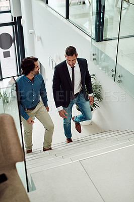 Buy stock photo High angle shot of two businessmen walking up a staircase in an office