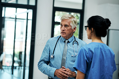 Buy stock photo Shot of two medical practitioners having a discussion in a hospital