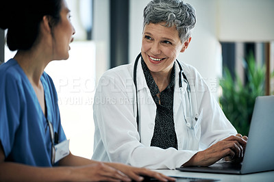 Buy stock photo Shot of two medical practitioners using a laptop in a hospital boardroom