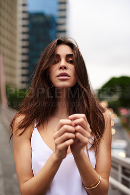 Buy stock photo Cropped portrait of an attractive young woman standing outdoors in the city during the day